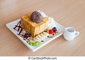 Honey toast and whipping cream with chocolate ice cream on wood background