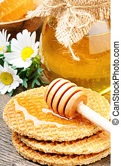 Honey waffles and wooden drizzler on wooden table