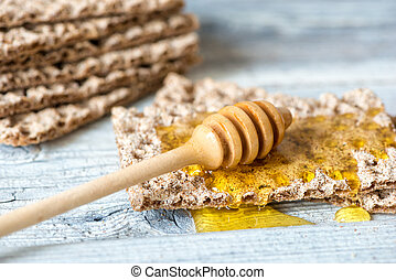 honey with dipper and crispbread on wooden background