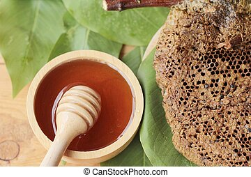 Honey with honeycomb on green leaves.