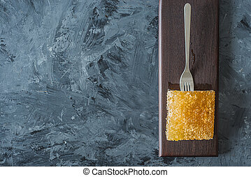 Honeycomb on brown plate on grey with black background