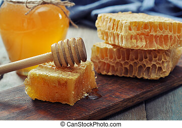 Honeycomb with honey dipper on vintage wooden background