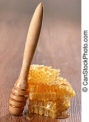 honeycombs and drizzler on wooden background