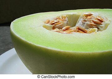 Close up of a honeydew melon on a plate.