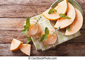 Honeydew melon juice closeup on wooden background,...