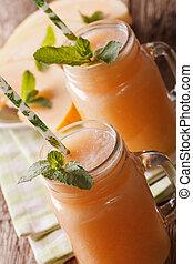 Honeydew melon juice closeup on wooden background, vertical...