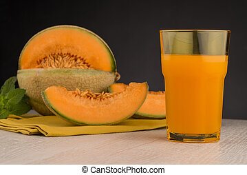 Honeydew melon juice on a wooden table background.