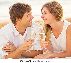 Honeymoon concept, Man and Woman in love, Couple enjoying glass of champagne on tropical beach at sunset