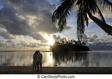 Honeymoon couple looks at the sunrise from a tropical pacific island beach in Muri lagoon in Rarotonga Cook Islands