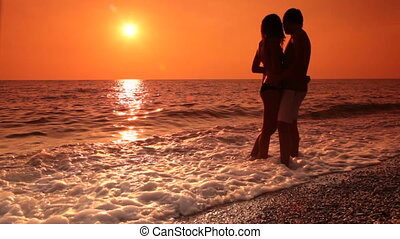 Honeymoon couple on the beach at sunset