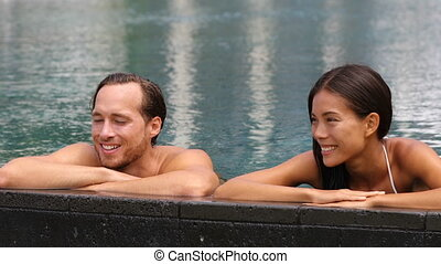 Honeymoon couple relaxing together in an infinity swimming pool in luxury resort spa retreat beach destination. Luxurious hotel travel vacation. People relaxed enjoying summer holidays. 59.94 FPS.