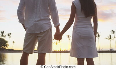 Honeymoon couple romantic at sunset holding hands in love enjoying vacation at beach looking at each other and water view hand in hand on travel holidays getaway. Mixed race couple. RED EPIC