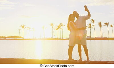 Honeymoon couple taking selfie romantic at sunset in love enjoying vacation at beach using smart phone holding around each other in embrace on travel holidays getaway. RED EPIC.