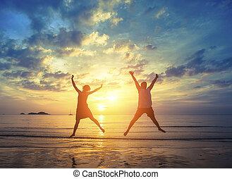 honeymoon., giovane coppia, saltare, su, il, mare, spiaggia, durante, strabiliante, sunset., vacanza, e, nature.