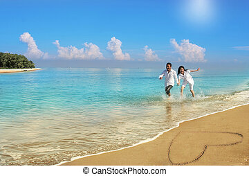 happy couple walking along beach