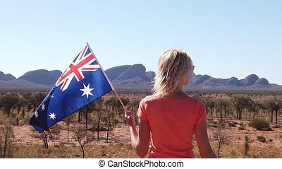 SLOW MOTION tourist woman with Australian flag by Mount Olga rock formation in Uluru-Kata Tjuta National Park in Northern Territory, Australia. Travel concept in Australian outback or Red Center