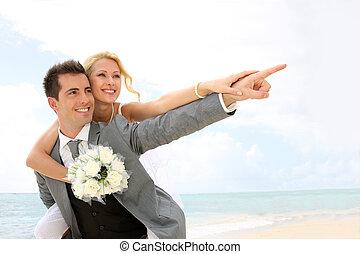 Honeymoon piggyback ride on the beach