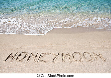 Honeymoon written on the sand