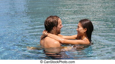 Honeymoon - young couple lovers in swimming pool on travel vacation in love enjoying romantic holidays, 59.94 FPS slow motion.,