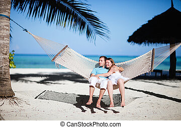 Honeymoon - Young romantic couple relaxing in hammock on...