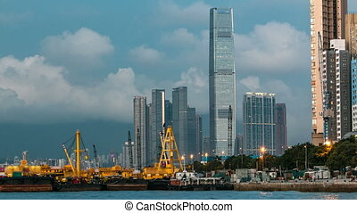 Hong Kong business center day to night timelapse with a cloudy blue sky before sunset