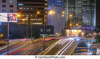 Hong Kong Business District timelapse at Night. Corporate building at the back and busy traffic across the main road at rush hour.