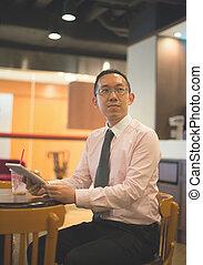hong kong business man having coffee at cafe with tablet , vinta