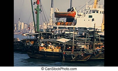 Historic colorful Chinese cargo ships with hanging clothes of the sailors for long travels. Hong Kong port Victoria Harbour. Historic restored archival footage on 1980s.