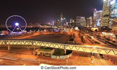 Spectacular aerial view of cityscape in Hong Kong, Central District, with Observation Ferris Wheel at Victoria Harbour illuminated at night. time lapse.