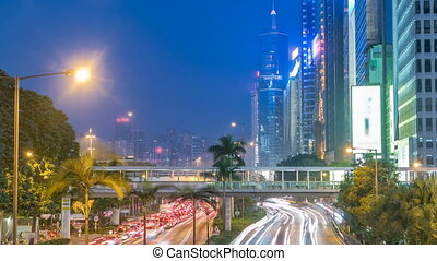 Hong Kong street with busy traffic and skyscraper office at dusk day to night timelapse.