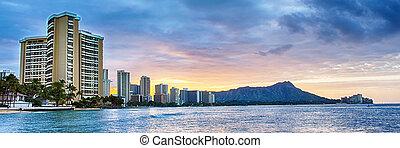 Early morning sunrise at dawn illuminates clouds over Diamond Head and Waikiki Beach area of Oahu in Hawaii