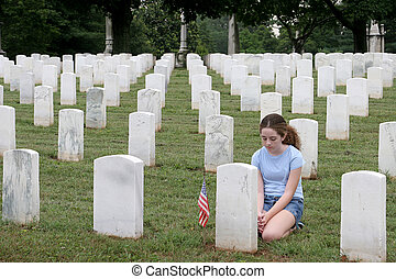 a young girl in a military cemetary honoring a fallen soldier