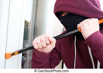 Hooded burglar forcing window to rob in the house