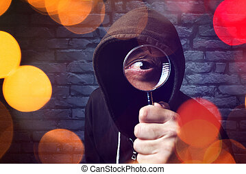 Hooded computer hacker with magnifying glass