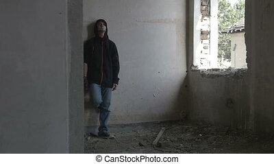 Hooded depressed young man sitting in an abandoned building