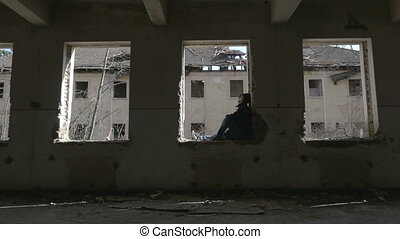 Hooded depressed young man sitting on the window frame of an...