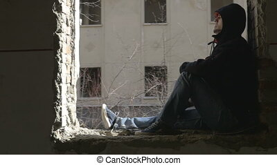 Hooded depressed young man sitting on the window frame of an abandoned building