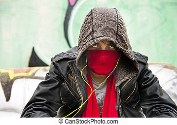 Hooded figure, wearing a scarf in front of his nose and mouth to disguise himself, looking menacing into the camera