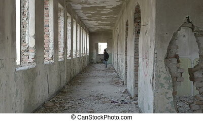 Hooded frightened young man running in an abandoned military building