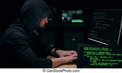 Hooded hacker programming on computer in dark room with devices, internet security, program code, security interference