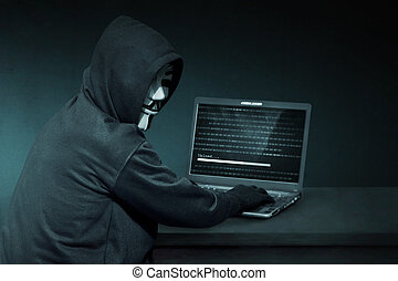 Hooded hacker with anonymous mask using laptop to steal data
