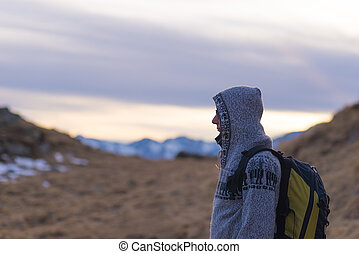Hooded lady with backpack resting on the Alps at sunset