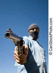 Hooded man with 44 magnum revolver threatening, wide angle view