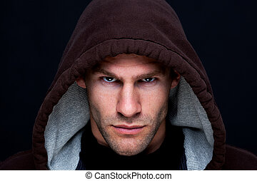 Headshot of a man wearing a brown hooded top with an intense stare