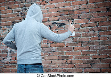 Hooded tagger writing graffiti on urban walls - Man writing...