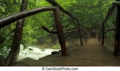 Hooded Tourist Walking On Bridge Hanging Above River