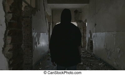 Hooded young man walking through the hallway of an abandoned building