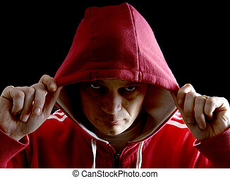 Hoodlum - A grim looking Hoodlumlifting his hood with his...