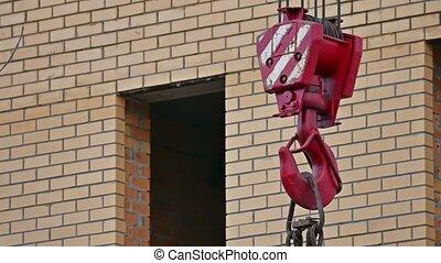 Hook crane sways in the wind behind brick house building...