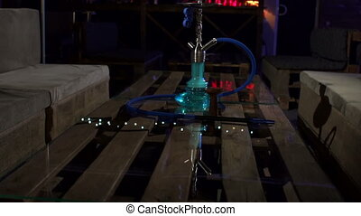 Hookah glass bottle for Smoking tobacco in cafes on Desk with blurred background